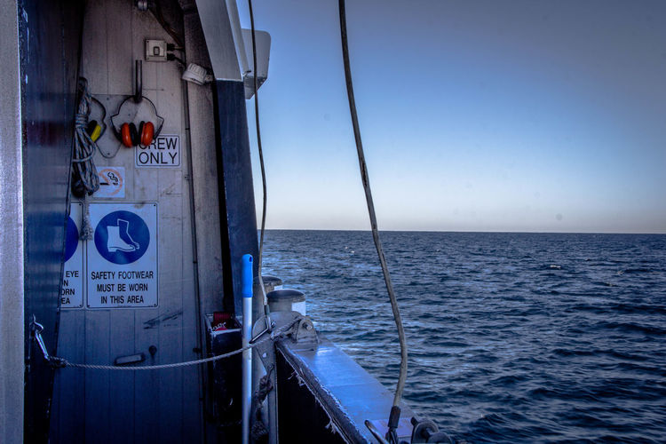 EyeEmNewHere Blue Clear Sky Crew Only Horizon Over Water Onboat Safety Ship Sign Text Transportation