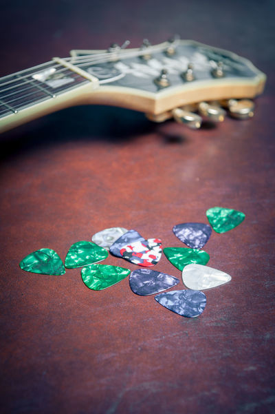 Bunch of guitar plectrums with guitar headstock in background Bunch Close-up Day Electric Guitar Guitar Headstock Heap Indoors  Many Music Brings Us Together Musical Equipment Musical Instrument No People Playing Plectrums Red Stringed Instrument Wooden Table
