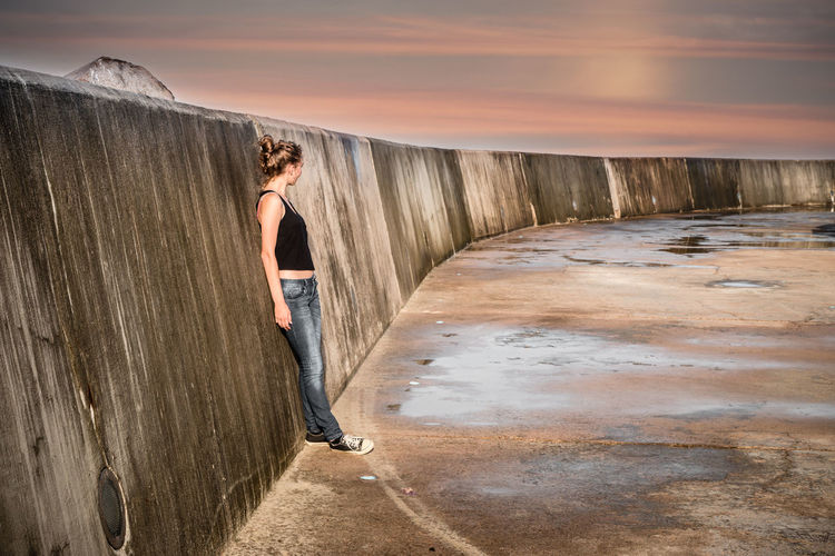 Woman standing on shore against sky during sunset