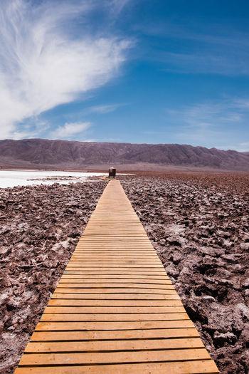 Footpath leading towards mountains against sky