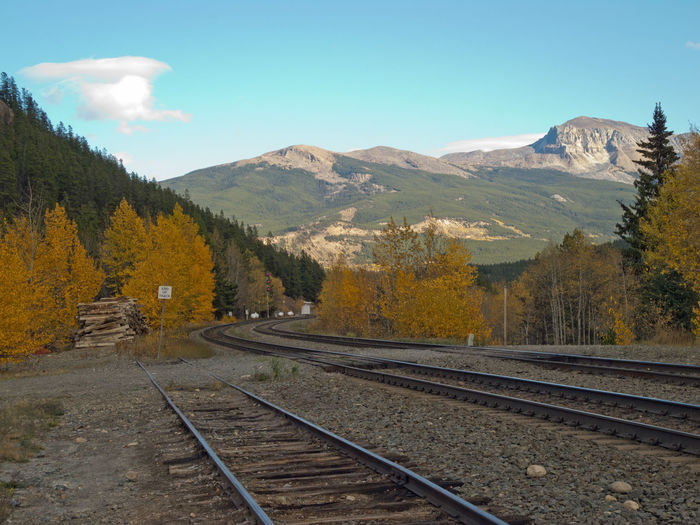 Railroad track by mountains against sky