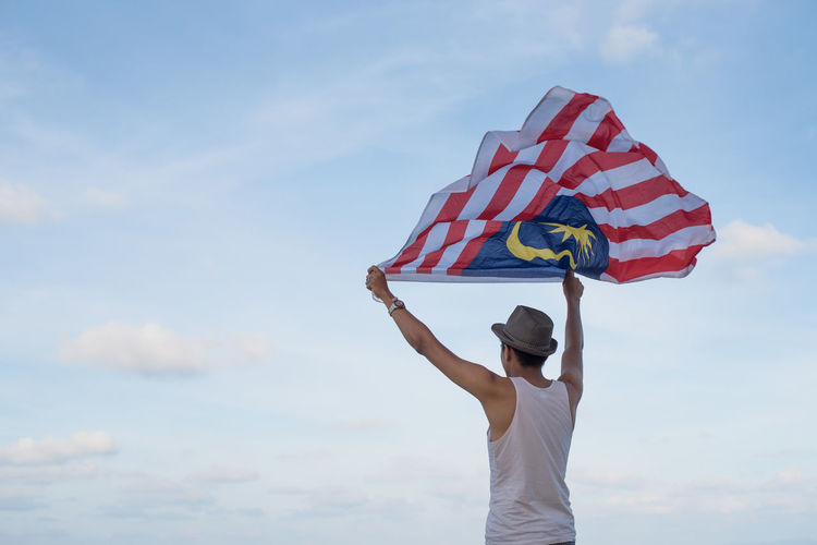 Rear view of man holding malaysian flag against sky