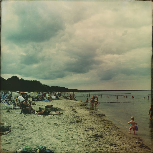 People relaxing at beach against cloudy sky