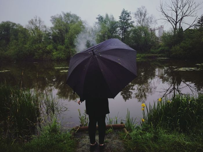 Chilling in the rain Water Lake Full Length Wet Protection Rear View Extreme Weather Reflection Rainy Season Umbrella Rainfall Rain