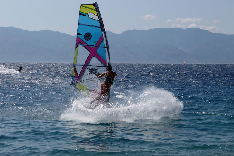 Woman windsurfing in sea against sky