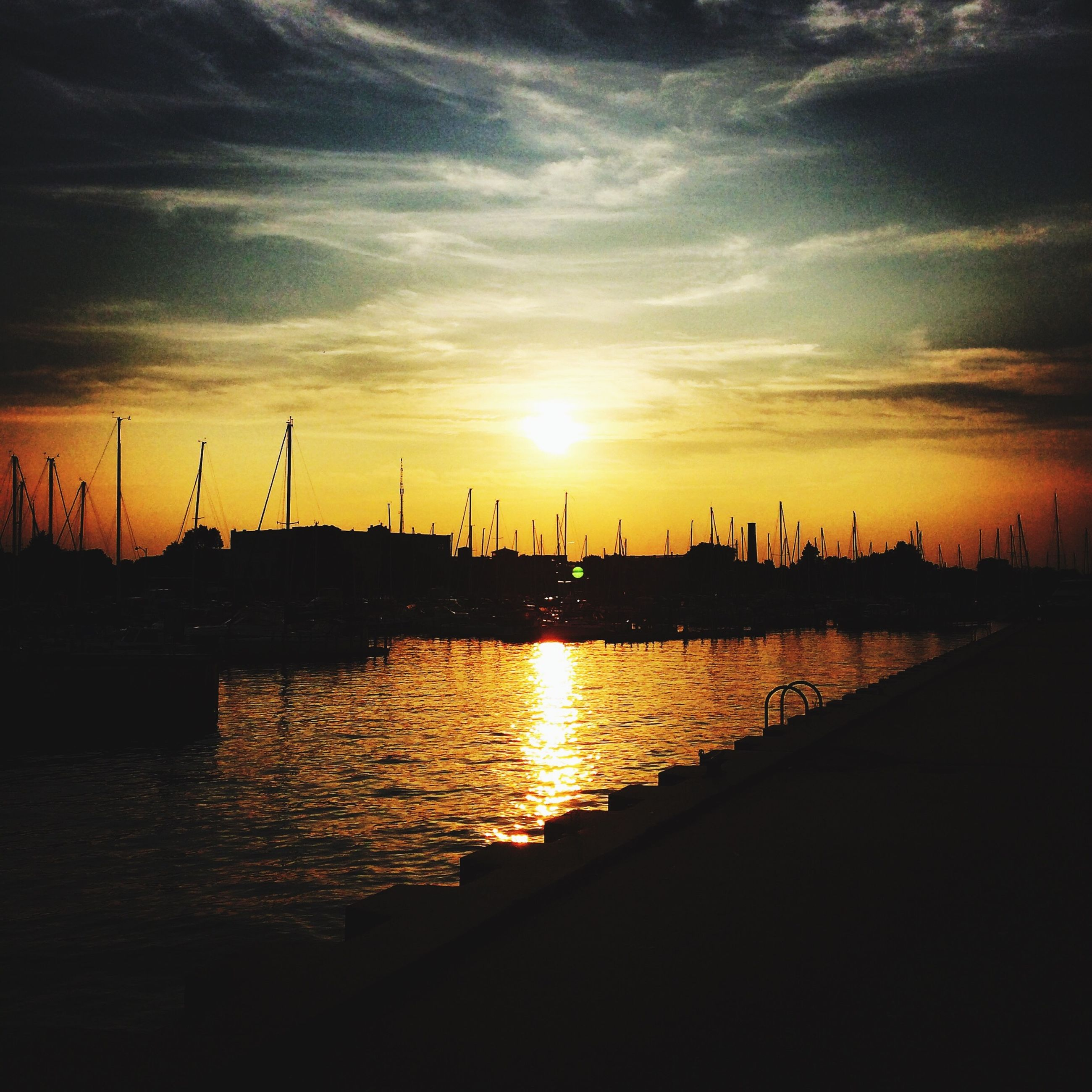 sunset, water, silhouette, sun, sky, reflection, scenics, river, beauty in nature, orange color, sunlight, harbor, tranquil scene, cloud - sky, nature, waterfront, sea, built structure, tranquility, cloud