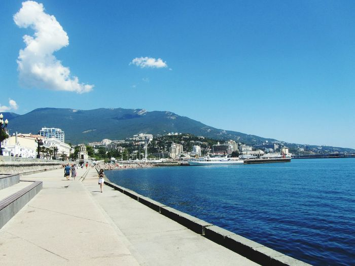 Scenic view of sea by town against blue sky