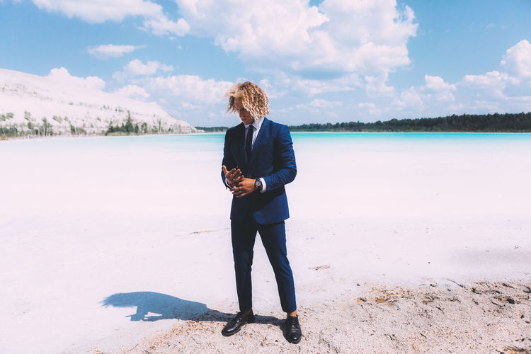 Blond curly guy dressed in business suit is posing on the crystal clear lake. Trendy hairstyle, awesome shoot. Summer time. Beach Beauty In Nature Casual Clothing Cloud - Sky Day Full Length Hairstyle Land Leisure Activity Lifestyles Nature One Person Outdoors Real People Scenics - Nature Sky Standing Water Young Adult