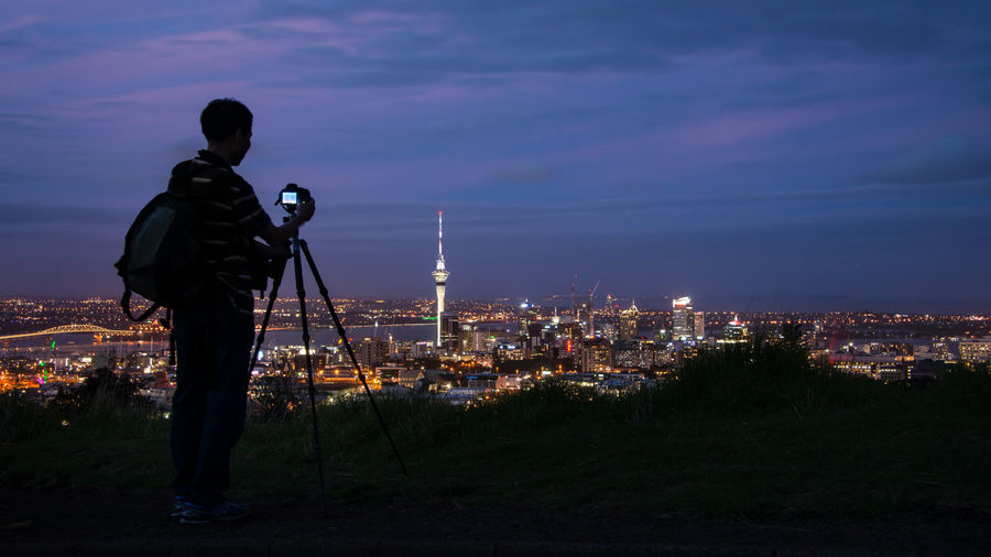 Rear view of man photographing cityscape against sky at night