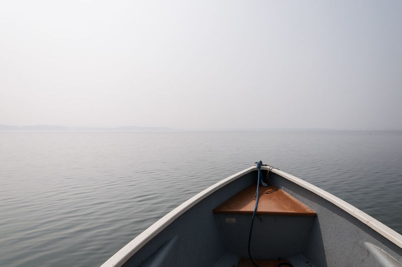 Rowboat in lake against sky during foggy weather