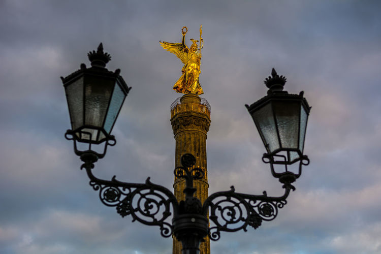 Low angle view of victory column and street light against cloudy sky
