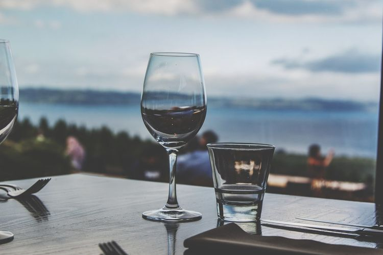 Wineglass on table at restaurant with sea seen through window