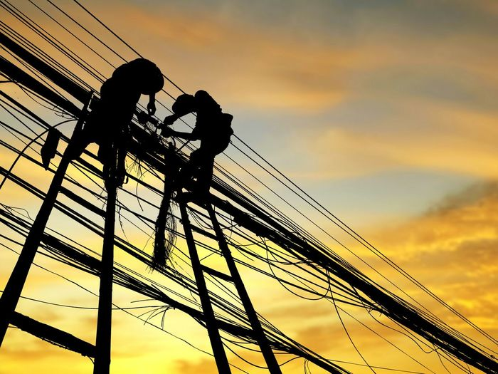 Low angle view of silhouette men working on power cables against orange sky