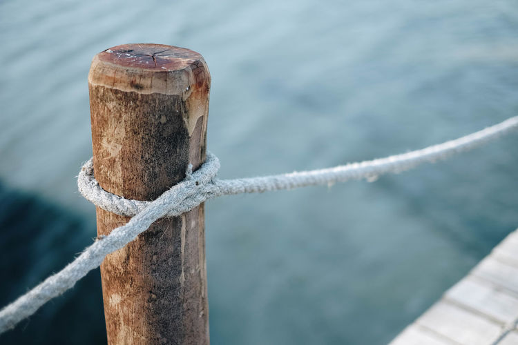 Close-Up Of Rope Tied To Wooden Post At Harbor