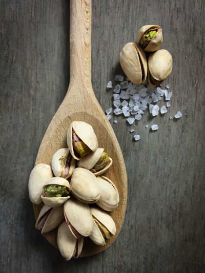 High Angle View Of Pistachios On Wooden Spoon
