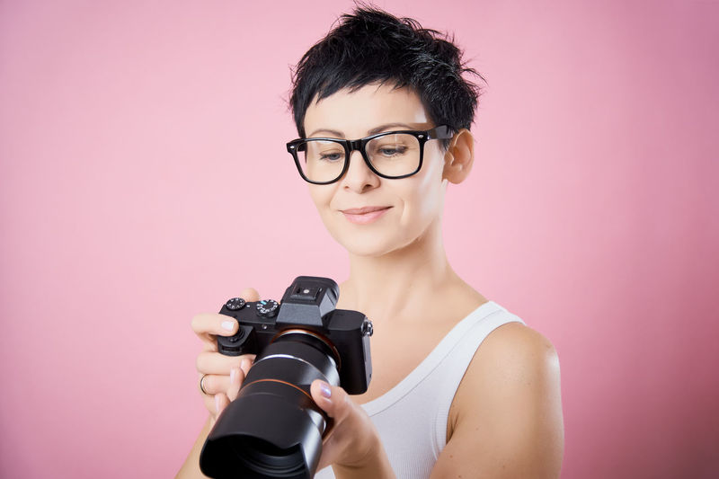 Portrait Studio Shot Colored Background Indoors  Looking At Camera Glasses Eyeglasses  Young Adult Camera - Photographic Equipment One Person Headshot Technology Photography Themes Holding Pink Background Smiling Adult Women Front View Beautiful Woman Hairstyle Photographer Digital Camera Camera Camera - Photographic Equipment