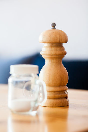 Close-up of pepper mill and salt on table