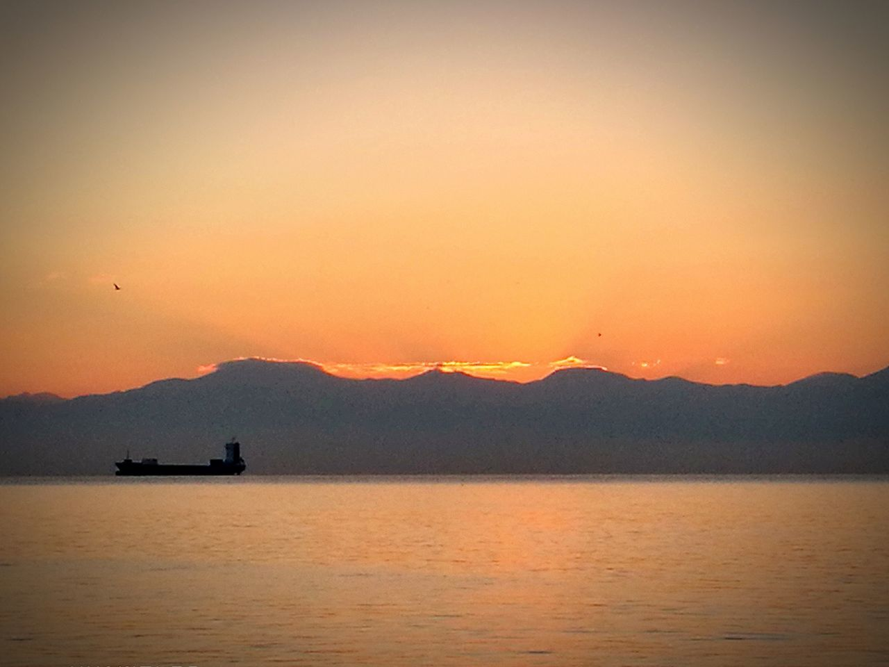 sunset, nature, beauty in nature, scenics, water, mountain, tranquility, silhouette, transportation, orange color, nautical vessel, waterfront, tranquil scene, mode of transport, sea, outdoors, no people, sky, mountain range, sailing, day, drilling rig, oil pump