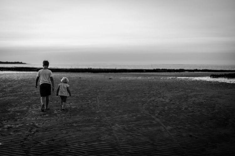 Rear view of two people standing on beach