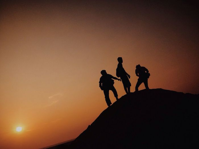 Silhouette of hikers on hill