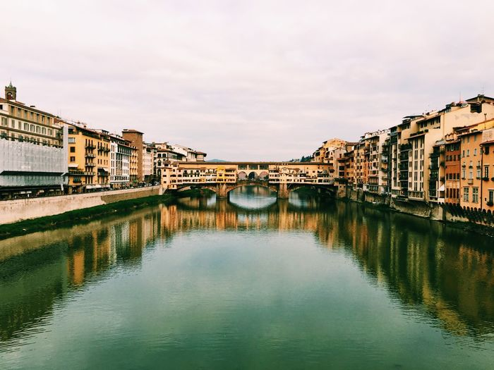 Ponte Vecchio Over Arno River Against Cloudy Sky