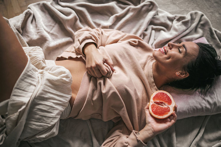 Portrait of young woman lying on bed