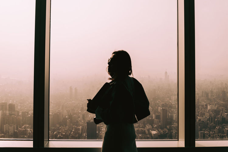 Woman standing by window against clear sky