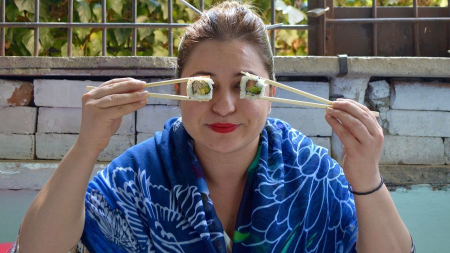 Close-up of woman having sushi with chopsticks