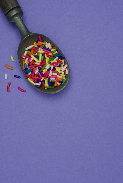 A metal ice cream scoop filled with colorful sprinkles on a purple background. Dessert Green Color Red Sugar Blue Candy Copy Space Food Food And Drink Ice Cream Scoop Multi Colored No People Purple Background Sprinkles Still Life Studio Shot Sweet Food Sweets Topping White Color