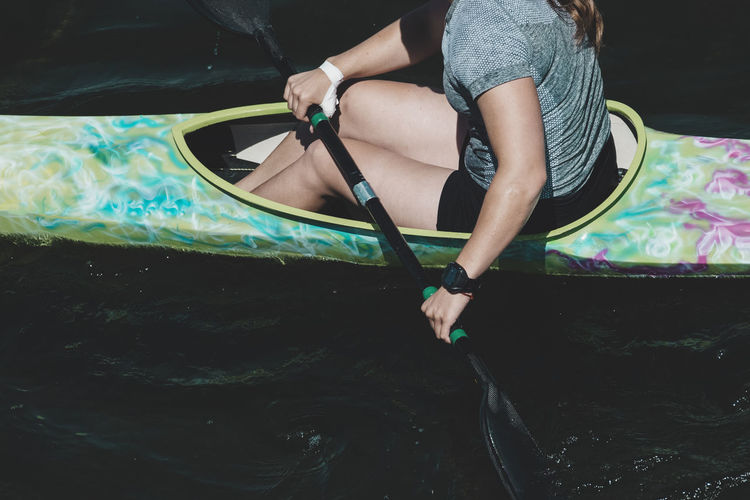 Low section of woman sitting in kayak