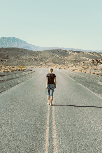 Rear view of woman walking on road against sky