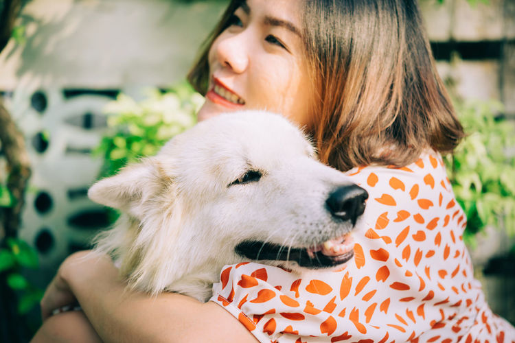 Close-up of smiling woman holding dog