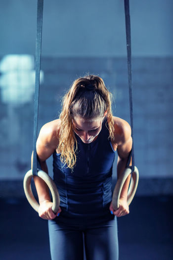 Female athlete exercising with gymnastic rings in gym