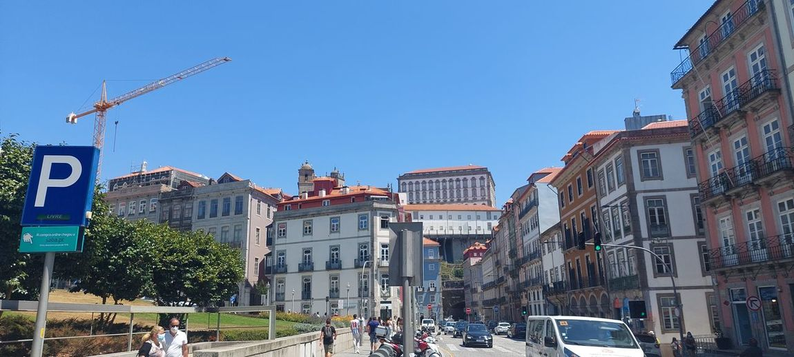 Panoramic view of buildings in city against clear blue sky