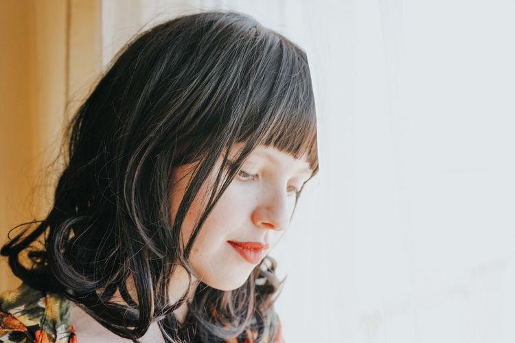 Close-up of beautiful woman at window