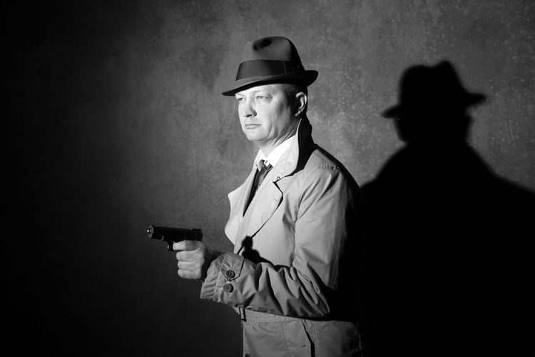 Man Wearing Trench Coat And Hat Pointing Gun At Night