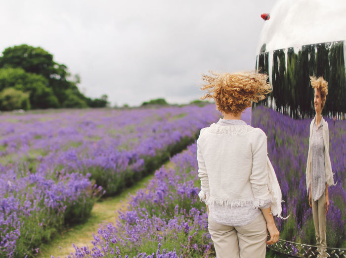 Rear View Of Woman Standing Against Chrome Trailer With Reflection On Lavender Field