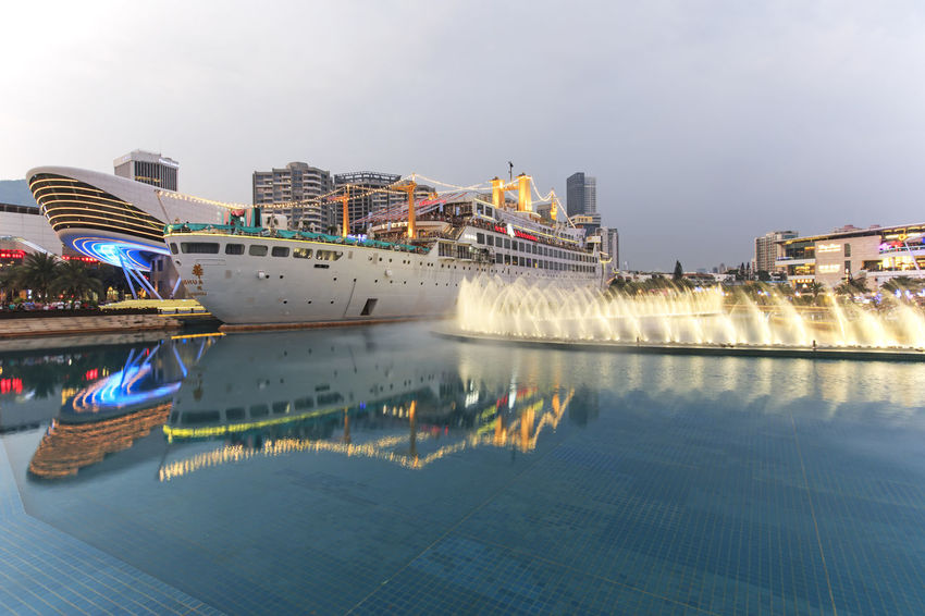 "Shenzhen, China - August 22,2015: Dancing Fountains in New Sea World Plaza, one of the landmark of Shenzhen, at sunset with the Minghua ship on its center. The ship was originally known as Anceevilla and was later renamed ""Minghua"" by the chinese who bought it. Anceevilla Architecture ASIA Blue Built Structure China City City Life Cloud - Sky Dancing Fountain Day Guandong City Modern Nature No People Outdoors Reflection Shenzhen Shenzhen.China Sky Standing Water Stock Market Travel Destinations Water Waterfront"