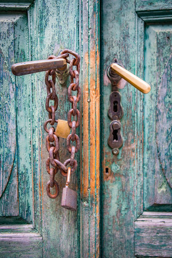 Close-up of old wooden door with rusty padlock and chain
