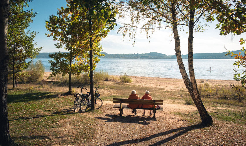 couple on bench observing stand-up surfer at beautiful autumn lake Wallpaper Stand-up Paddling Tranquil Couple Older  People Warm Adventure Vacations View Sunlight Shadow Trees Beautiful Place Orange Leaves Autumn Tree Water Beach Relaxation Shadow Sky Outdoor Chair Bench Horizon Over Water Sand Sandy Beach Sunshade Calm