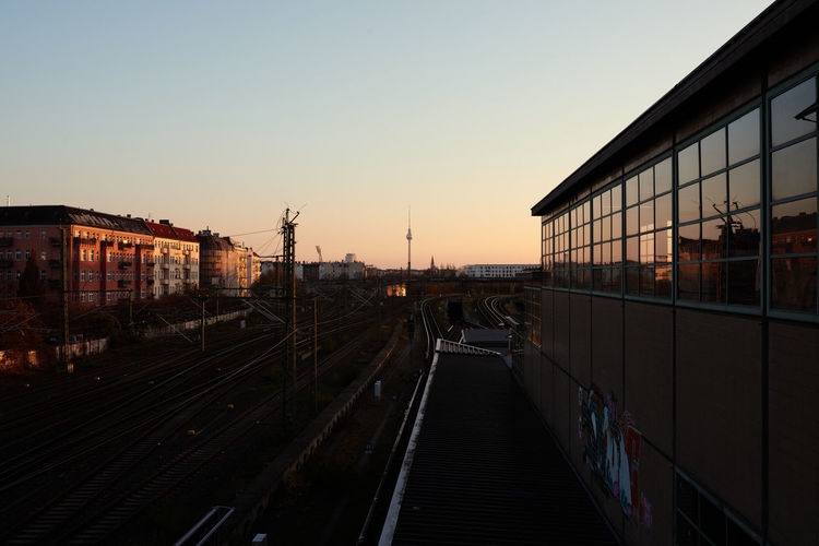 Railroad tracks in city against clear sky during sunset