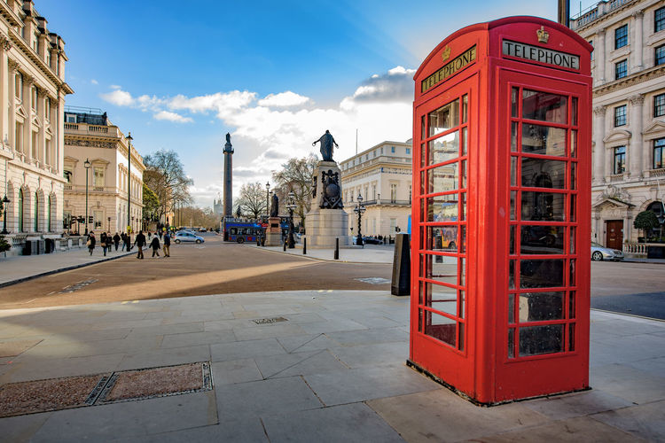 Traditional british telephone booth on sidewalk in city against sky