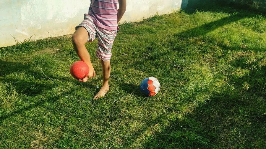 Low section of boy playing with ball on field