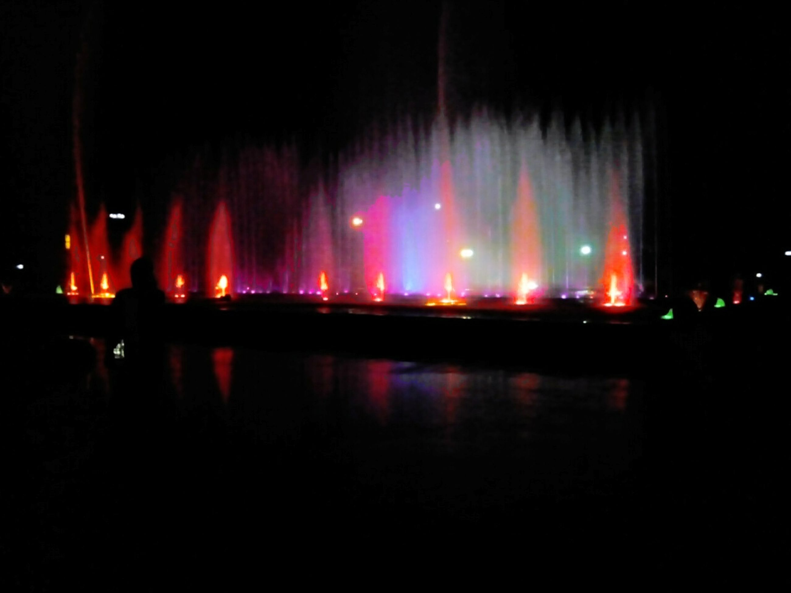 illuminated, night, reflection, indoors, water, lighting equipment, long exposure, motion, arts culture and entertainment, glowing, blurred motion, light - natural phenomenon, multi colored, in a row, dark, incidental people, waterfront, large group of people, light, copy space