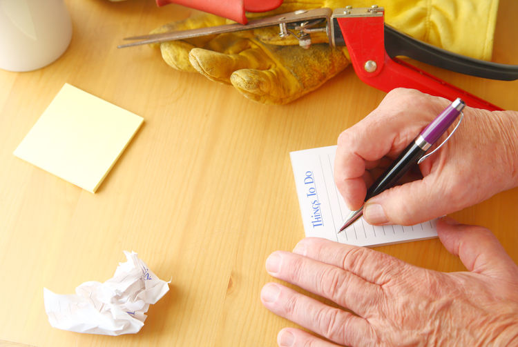 Cropped image of hands writing on paper at table