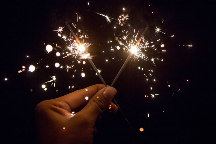 Cropped hand of person holding illuminated sparklers at night
