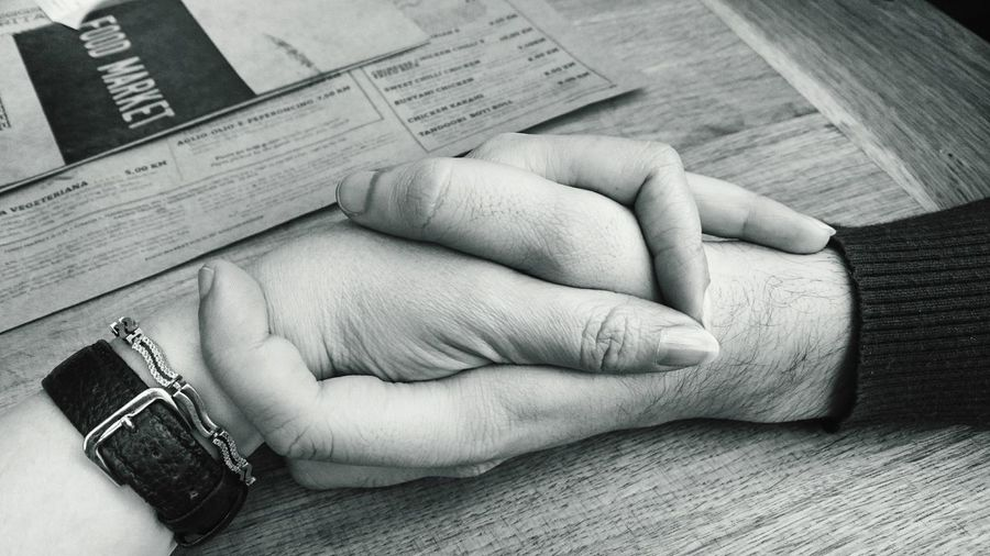 High angle view of man and woman holding hands at table