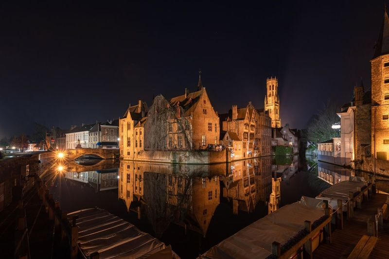 Illuminated buildings in bruges city at night