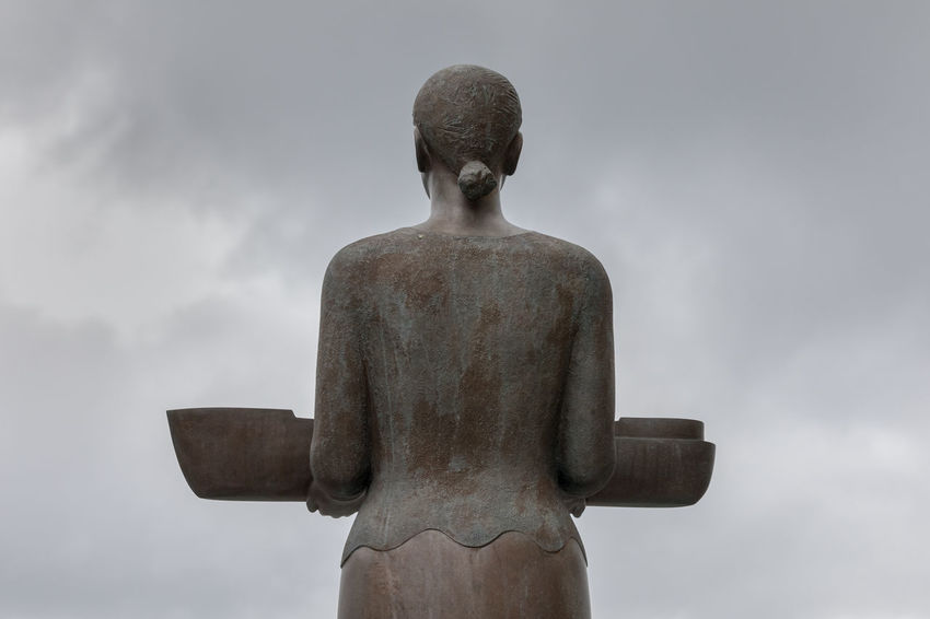 Rear view of sculpture: woman holding a boat and looking towards the sea Moody Sky Part Of Rear View Statue Built Structure Close-up Cloud - Sky Day Female Likeness Gray High Section Holding Human Representation Low Angle View Man Made Structure Metal Nautical Vessel No People Outdoors Overcast Sculpture Sea Ship Sky Statue