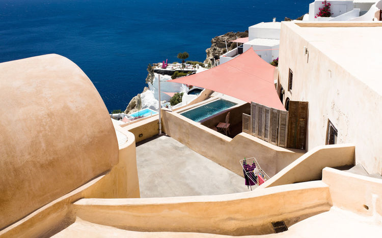 Architecture Building Building Exterior Building Terrace Built Structure Chair Day High Angle View Nature No People Outdoors Pool Santorini Sea Sunlight Swimming Pool Travel Destinations Water